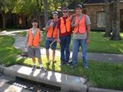 Volunteers in orange vests standing next to a storm drain